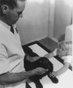Doctor Robert Burns, DVM, examines small dog with child looking on